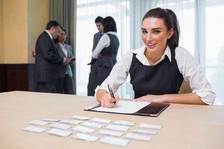 Smiling woman at welcome desk at business conference Stock Photo - 18120482