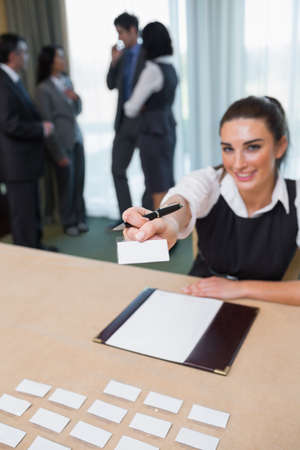 Woman handing you a name tag at business conference photo