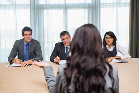 interviewed: Woman being interviewed for new job by panel of business people