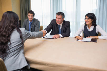Interviewee shaking hands with panel member in conference room photo