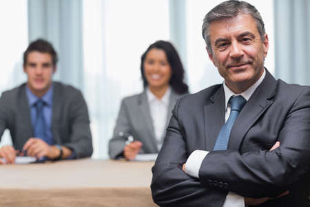 Businessman with arms crossed sitting with business panel in conference room Stock Photo - 18120590