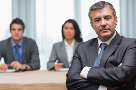 hotel staff: Serious businessman with arms crossed with interview panel in conference room Stock Photo