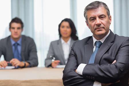 manager: Serious Gesch�ftsmann mit gekreuzten Armen mit Interview-Panel im Tagungsraum