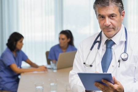 Smiling doctor with tablet at a meeting photo