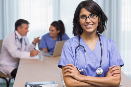 Smiling nurse with arms crossed in a meeting photo