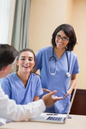 Nurses laughing with doctor using laptop in a meeting Stock Photo - 18120861