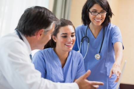Doctor and nurses looking at laptop happily in a meeting