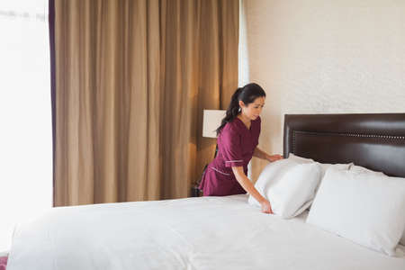 bed sheet: Hotel maid making the bed in hotel room