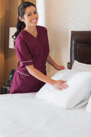 Smiling hotel maid making bed in hotel room photo