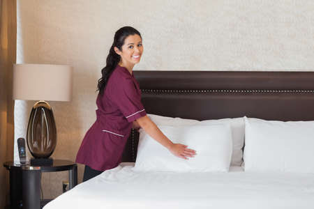 Happy hotel maid at work in hotel room photo