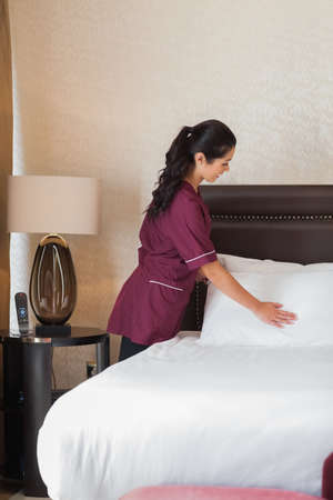 Hotel maid fixing pillows in hotel room photo