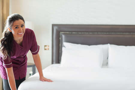 housekeeping: Hotel maid making up the bed in hotel room