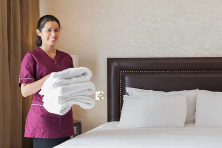 Hotel maid holding pile of fresh towels in hotel room Stock Photo - 18120840