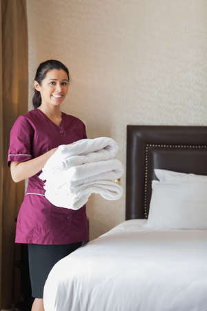 Smiling hotel maid holding towels in hotel room Stock Photo - 18120836