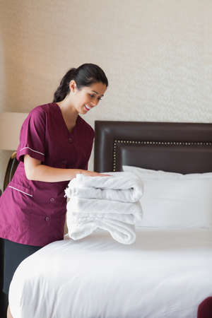 Hotel maid putting towels on bed in hotel room photo