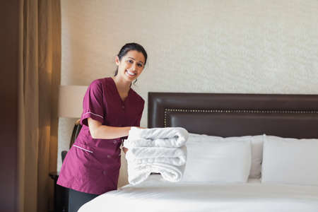 Happy maid working in hotel room holding pile of towels photo