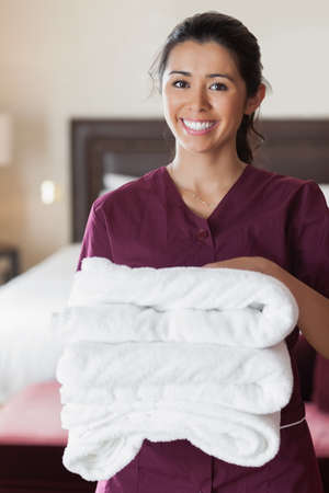 Smiling maid with towels in hotel room photo