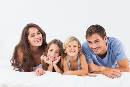Happy family lying on a bed together in the bedroom photo