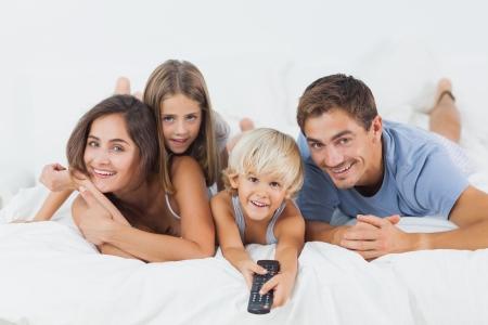 personas viendo television: Familia que miente en la cama con un mando a distancia en el dormitorio Foto de archivo