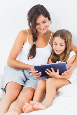 daughter mother: Mother and her daughter using a tablet on the bed Stock Photo