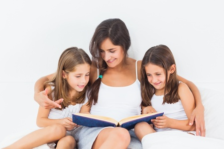 Mother and her children looking at a photo album in the bedroom Stock Photo - 18121370