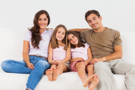 Cute family sitting on a sofa in the living room photo