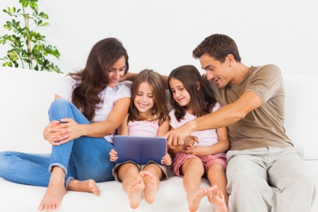Smiling family using a digital tablet on a sofa photo