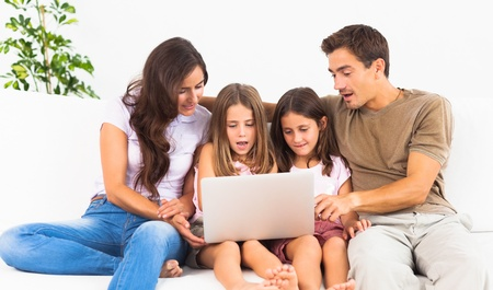 Family posing on a sofa with the laptop in the living room Stock Photo - 18121663