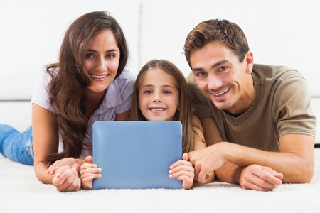Family with tablet  lying on a carpet in the living room photo