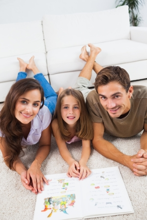 Family with a book lying on a carpet in the living room Stock Photo - 18121967