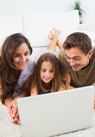 Family lying on a carpet with the laptop in the living room photo