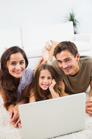 Smiling family lying on a carpet with the laptop in the living room Stock Photo - 18121664