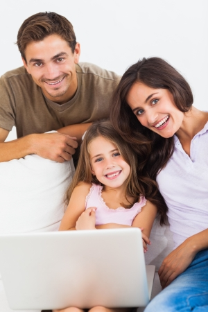 Happy family using the laptop sitting on a sofa photo