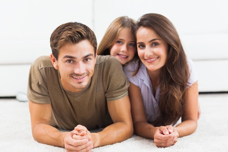 Family posing lying on a carpet in the living room Stock Photo - 18121711