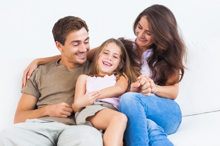 woman couch: Smiling family playing together on a sofa in the living room