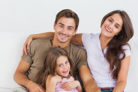 Happy family sitting together on a sofa in the living room Stock Photo - 18121775