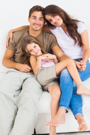 Cute family sitting together on a sofa in the living room photo