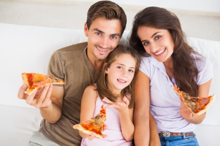 eating pizza: Family eating pizza on a sofa