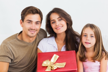 Father and his daughter offering a gift to her mother in the living room Stock Photo - 18122079