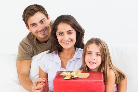 Parents offering a gift to their daughter on a sofa Stock Photo - 18121659