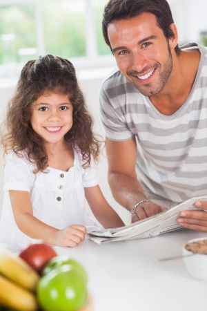 Dad and daughter reading a newspaper during breakfast in kitchen photo
