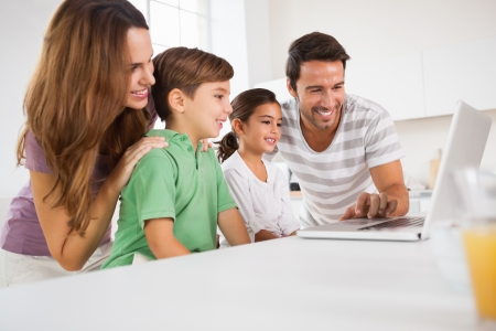 multiracial family: Happy family using a laptop in kitchen Stock Photo