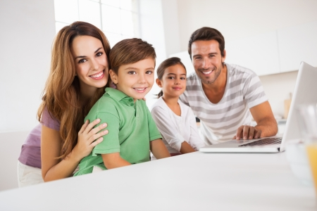 multiracial family: Happy family looking at the camera with a laptop in kitchen