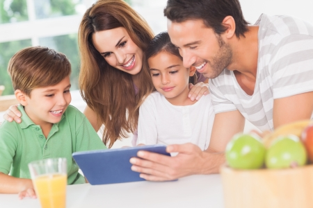 multiracial family: Family using a tablet pc in kitchen Stock Photo