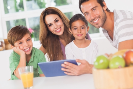 multiracial family: Happy family using a tablet pc in kitchen
