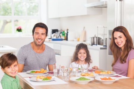 Smiling family having dinner in kitchen photo