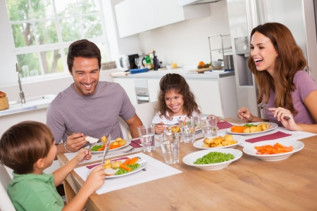 Family laughing around a good meal in kitchen photo