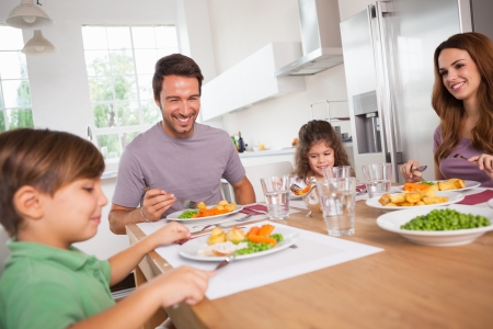 Family smiling around a good meal in kitchen photo