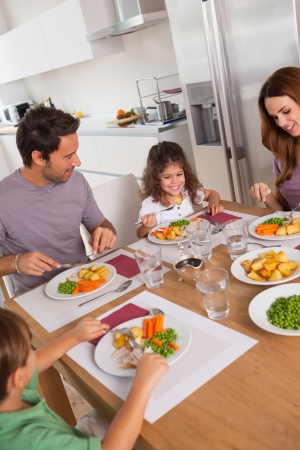 multiracial family: Family eating healthy dinner in kitchen