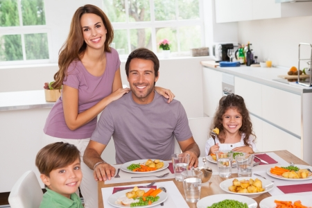 domiciles: Family smiling at the dinner table in kitchen